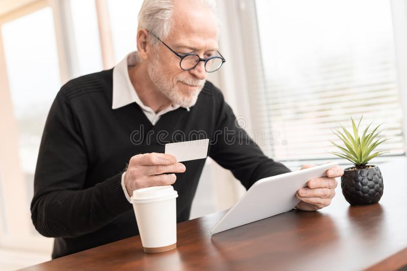 Man som använder den digitala minnestavlan och kreditkorten för online-shopping royaltyfri bild