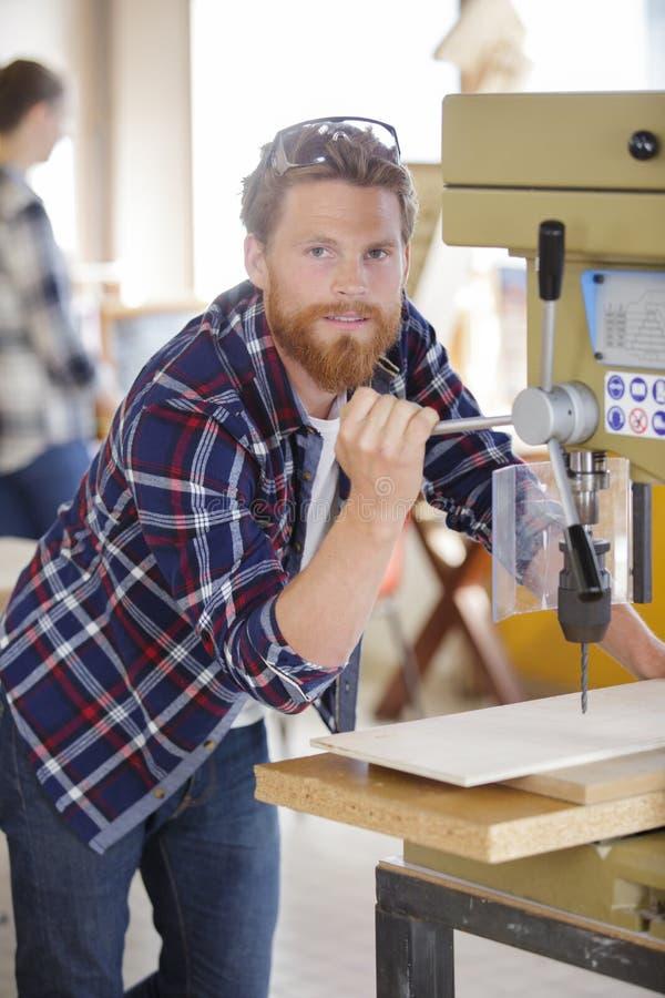 Man som använder den mala maskinen för att klippa trä royaltyfri fotografi