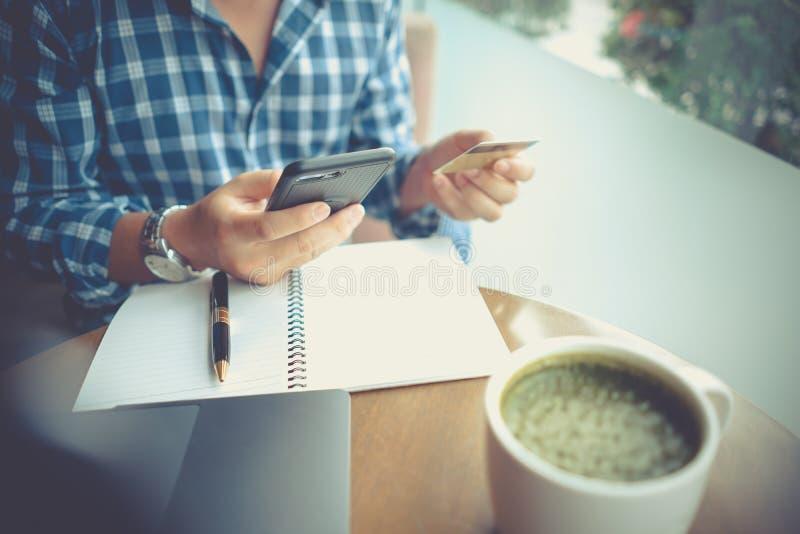 Man som använder den mobila smartphonen och kreditkorten för online-shopping i coffee shop, anteckningsbok för bärbar datordator  arkivbild