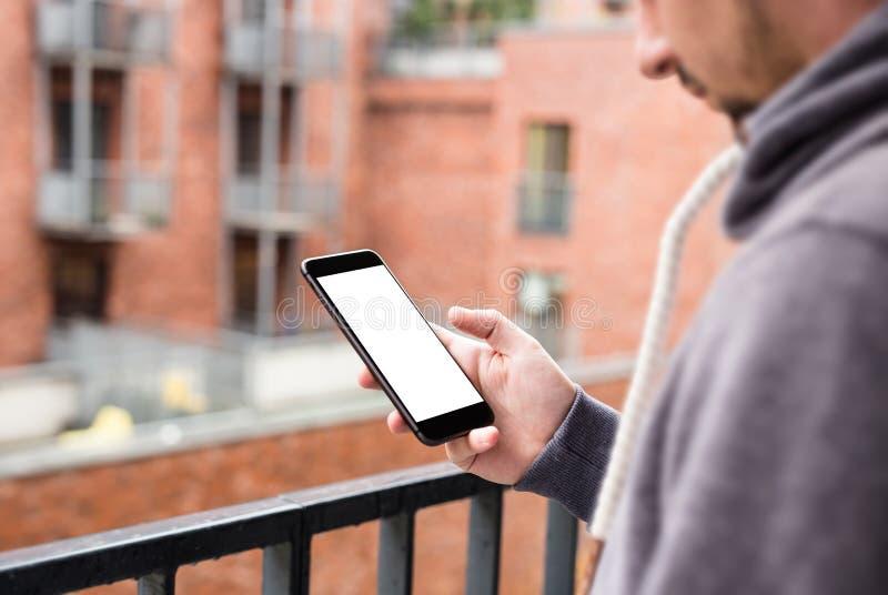 Man som använder den moderna mobila smartphonen Skott med tredje-person sikt, tom skärm royaltyfri foto
