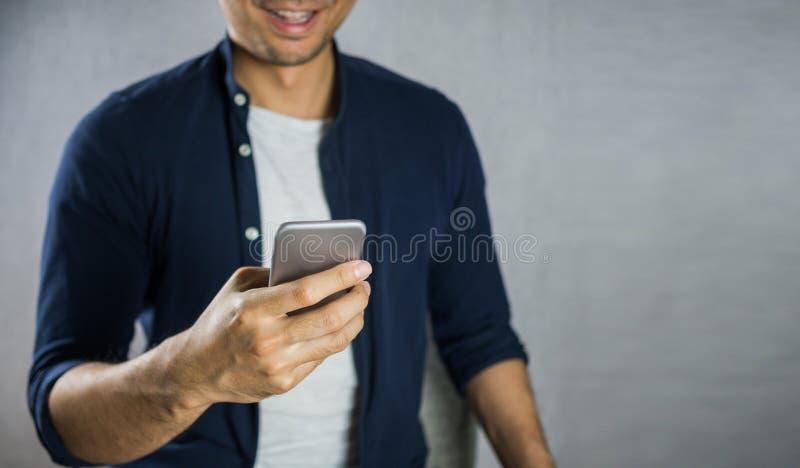 Man som använder den smarta telefonen och att le arkivfoton