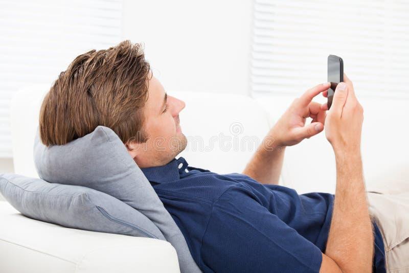 Man som använder den smarta telefonen på soffan royaltyfri fotografi