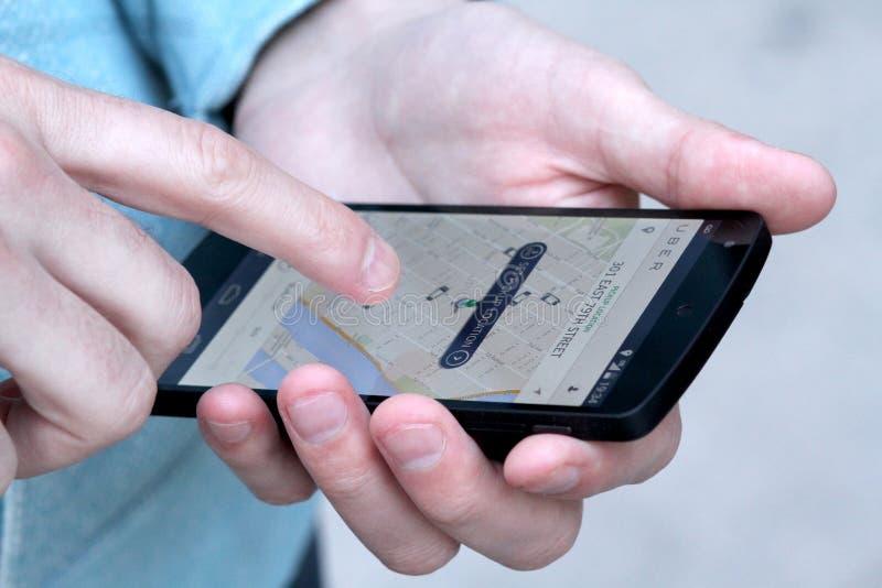 Man som använder den Uber mobilen App arkivfoto