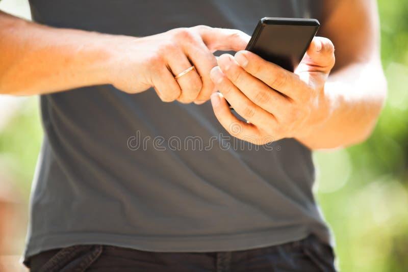Man som använder den utomhus- smarta telefonen för mobil arkivbild