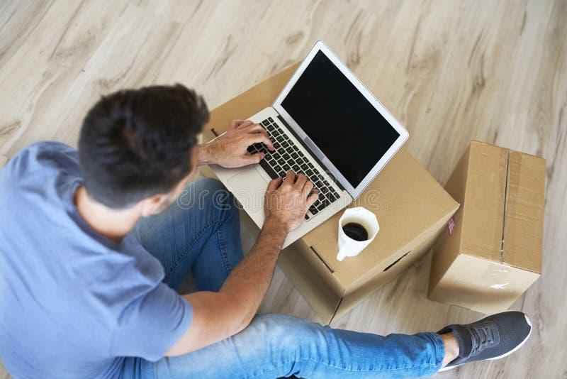 Man som använder en bärbar dator bredvid rörande askar royaltyfria foton