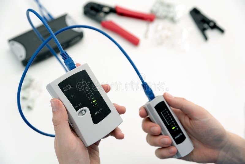 Man som använder en kvalificerad kabelkapacitetstester arkivfoto