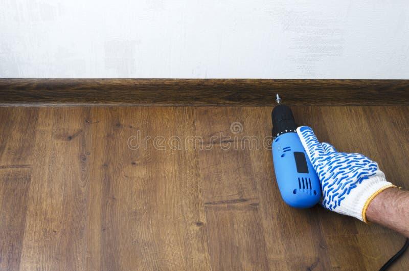 Man som använder en skruvmejsel för det kringgå brädet för golv, sockel Begrepp av reparationen Tomt avstånd för text royaltyfri fotografi