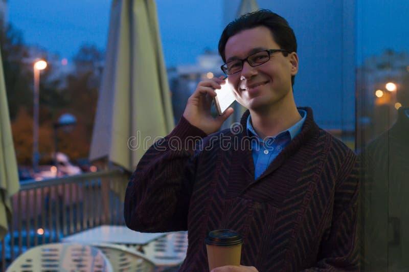 Man som använder en telefon som smsar på smartphonen app och den pappers- koppen kaffe för innehav royaltyfria foton