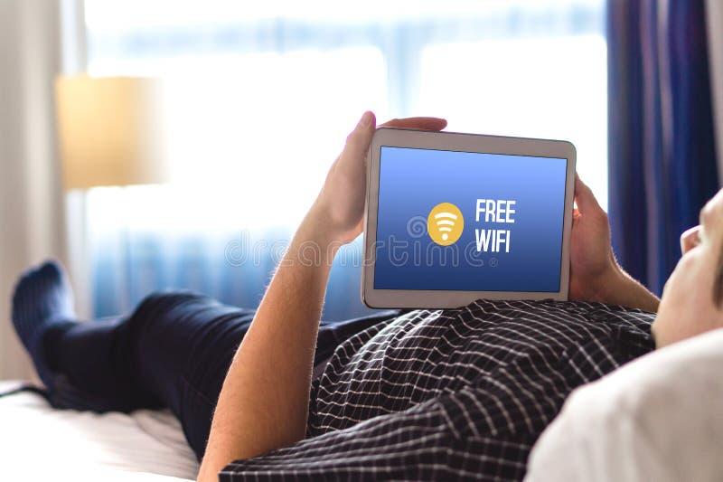 Man som använder fri hotellwifi med minnestavlan arkivfoton