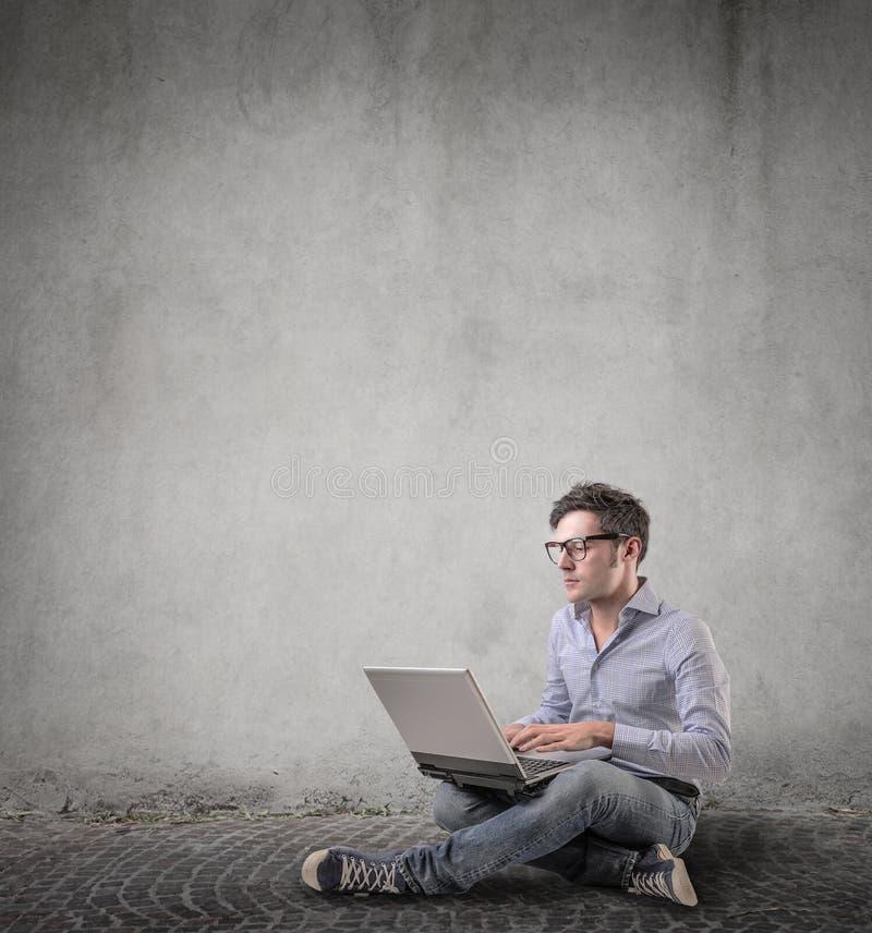 Man som använder hans bärbar dator royaltyfri bild