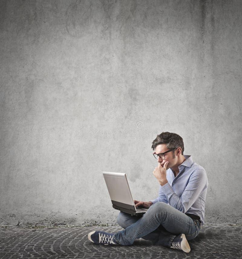 Man som använder hans bärbar dator arkivbild
