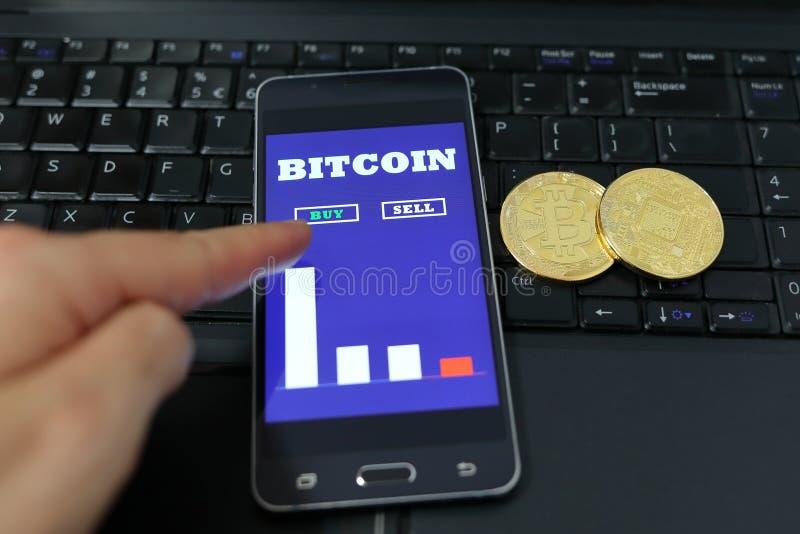 Man som använder hans smartphone för att köpa bitcoins Smartphone med för handeldiagram för bitcoin den kontanta på-skärmen Crypt arkivfoto