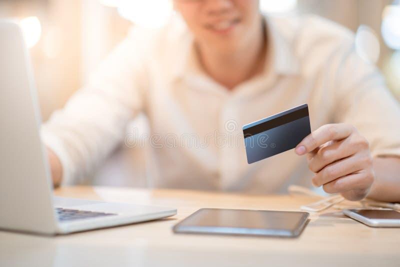 Man som använder kreditkorten för online-shopping royaltyfria bilder
