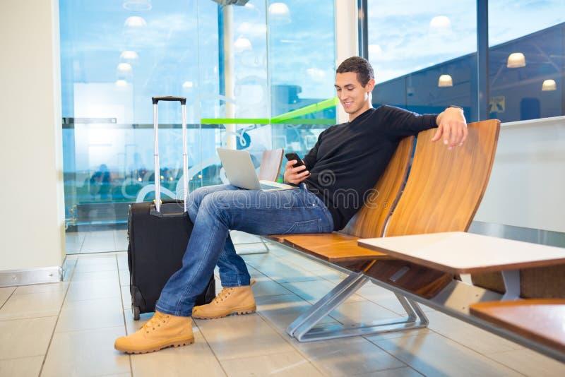 Man som använder mobiltelefonen i väntande område för flygplats fotografering för bildbyråer