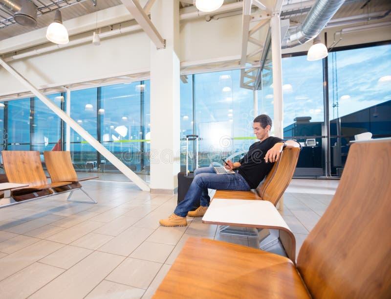Man som använder mobiltelefonen, medan vänta på hans flyg fotografering för bildbyråer