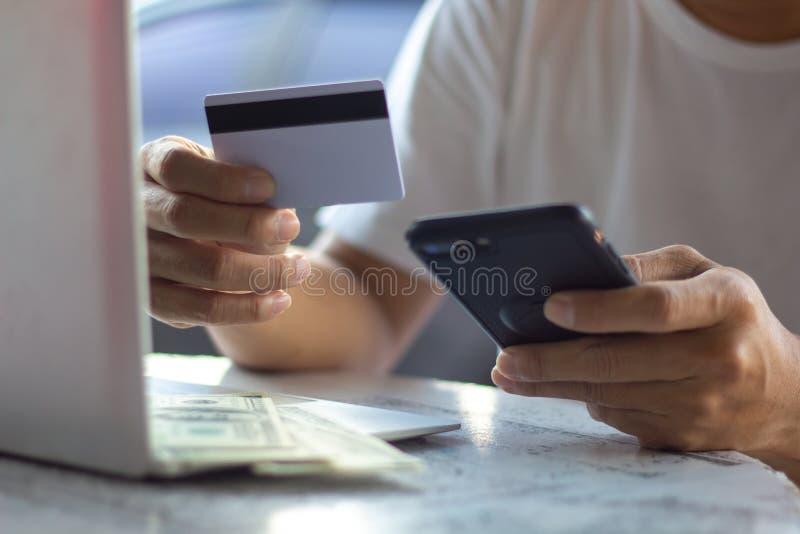 Man som använder mobiltelefonen och bärbara datorn som direktanslutet shoppar med kreditkorten Maninnehavkreditkort genom att anv arkivbild
