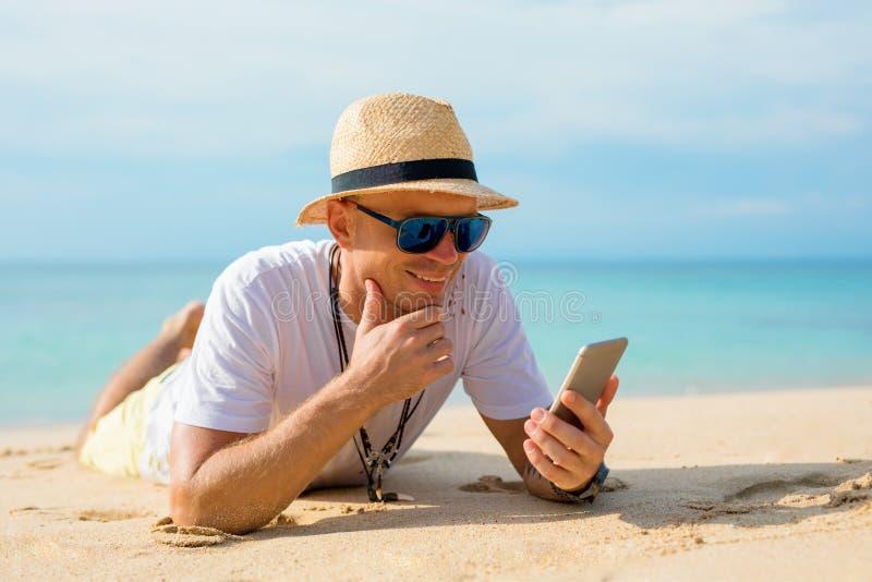 Man som använder mobiltelefonen på stranden fotografering för bildbyråer