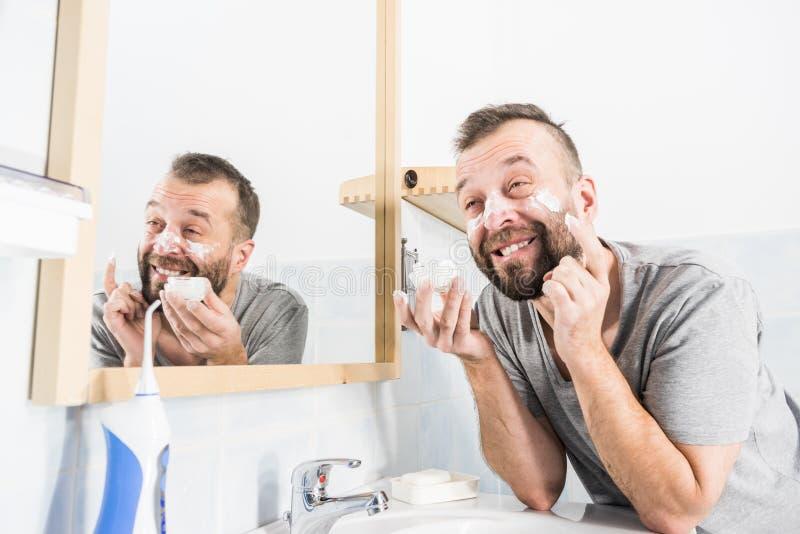 Man som använder moisturizer kräm i badrum arkivbild