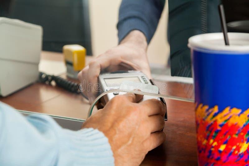 Man som använder NFC-teknologi för att betala för filmbiljetter arkivbilder