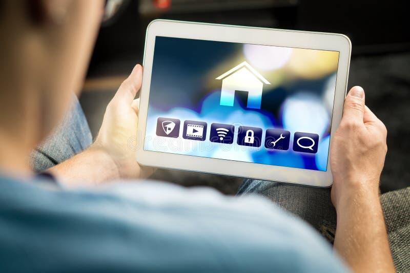 Man som använder smart hem- applikation i minnestavla för att kontrollera huset royaltyfri foto