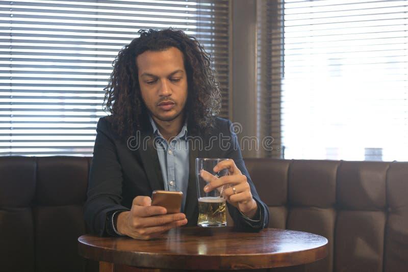 Man som använder smartphonen i en stång arkivfoto