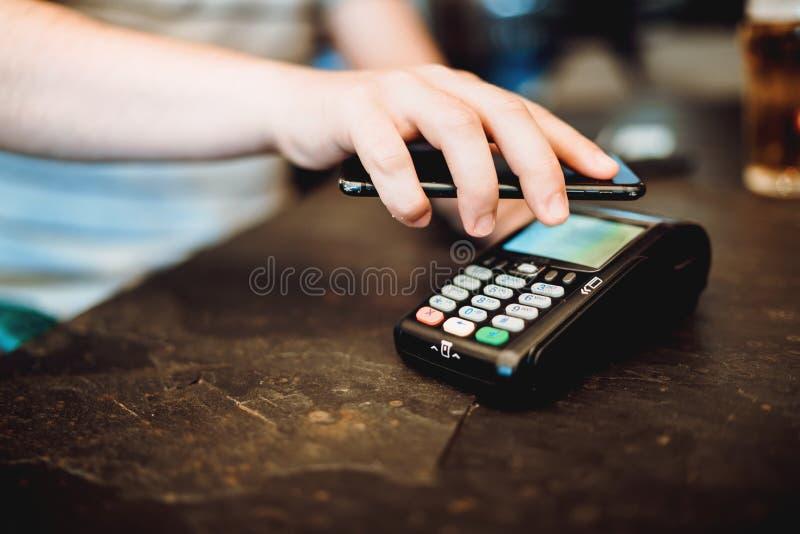 Man som använder smartphonen med nfcteknologi och betalar på restaurangen royaltyfri foto