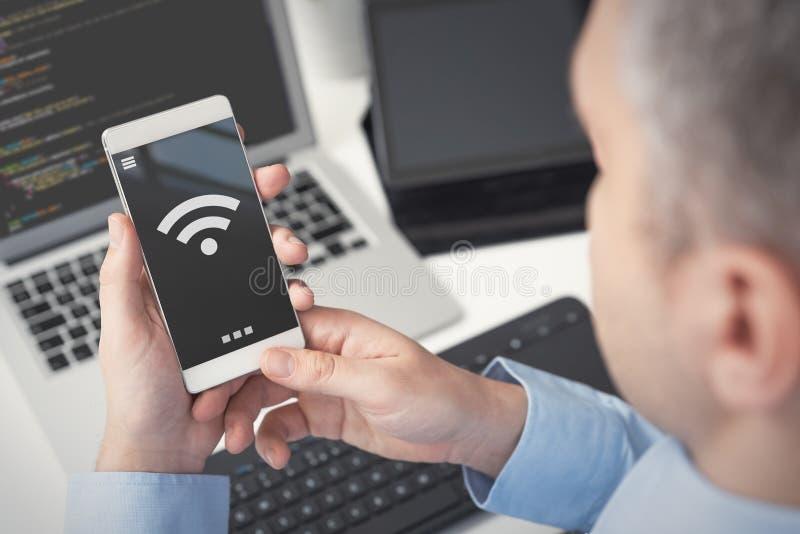 Man som använder smartphonen med trådlöst symbol arkivbild