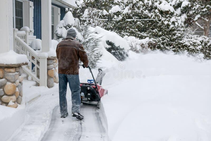 Man som använder snowbloweren i djup snö royaltyfria foton