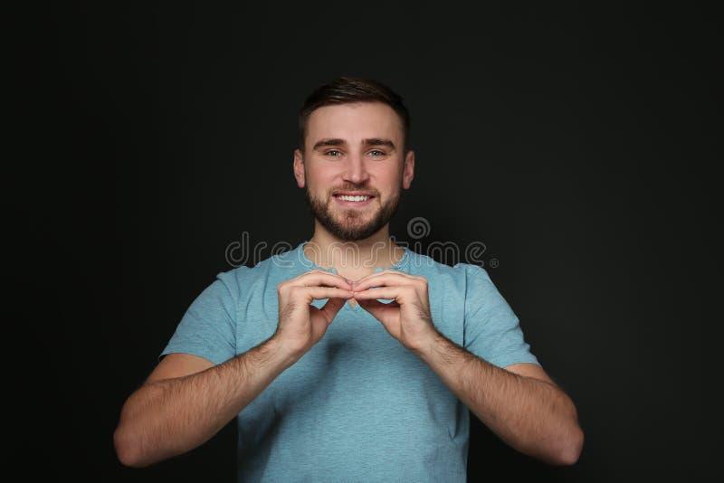 Man som använder teckenspråk på svart royaltyfri fotografi
