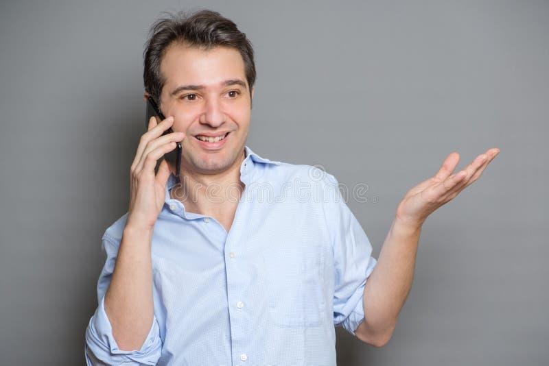 Man som använder telefonen som isoleras på en grå bakgrund royaltyfria bilder