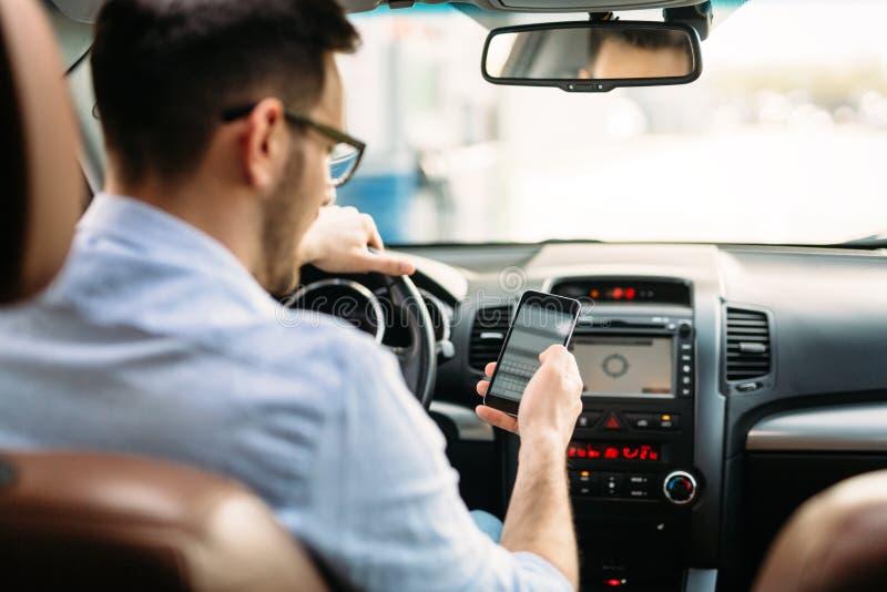 Man som använder telefonen, medan köra bilen royaltyfri fotografi