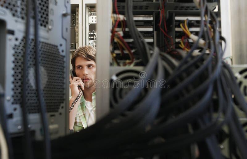 Man som använder telefonen som omges av datorutrustning royaltyfri fotografi