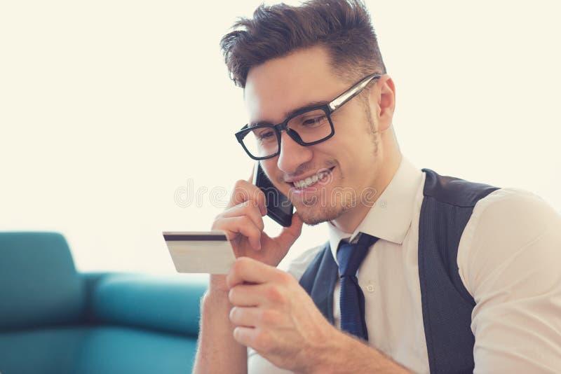 Man som använder telefontjänst och kreditkorten royaltyfri bild