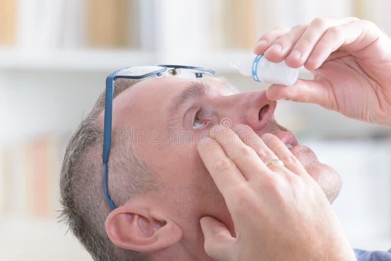 Man som applicerar ögondroppar royaltyfria foton