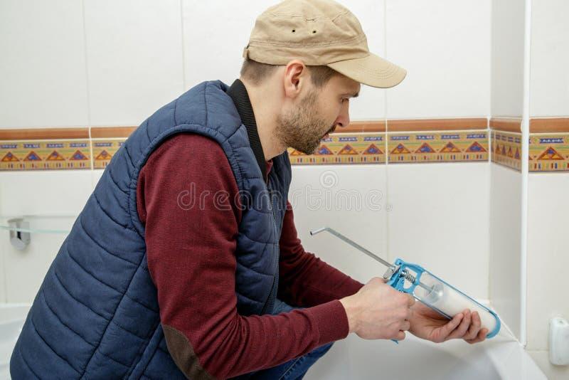 Man som applicerar silikontätningsmedel i badrummet arkivfoton