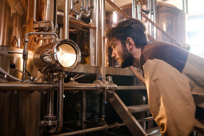 Man som arbetar i ett bryggeri arkivbild