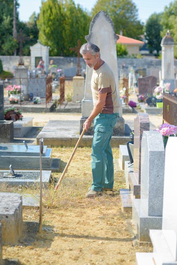 Man som arbetar i kyrkogård arkivbilder