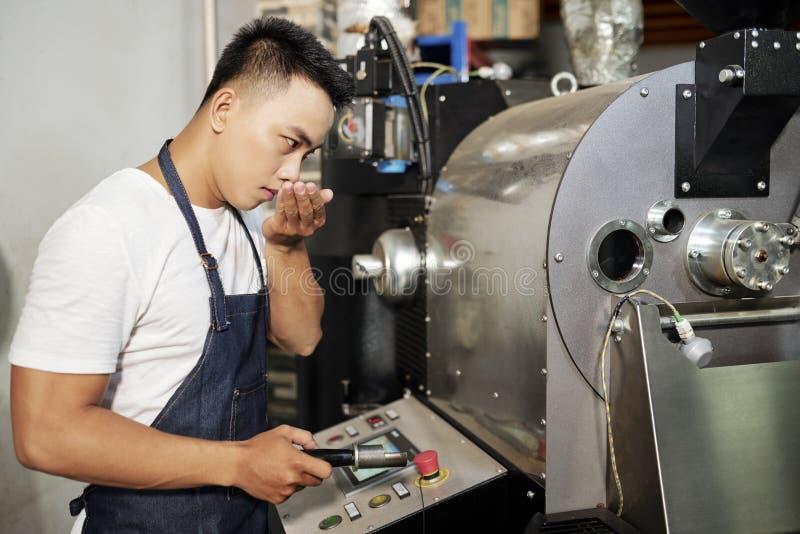 Man som arbetar i produktionen av att grilla kaffe arkivbild