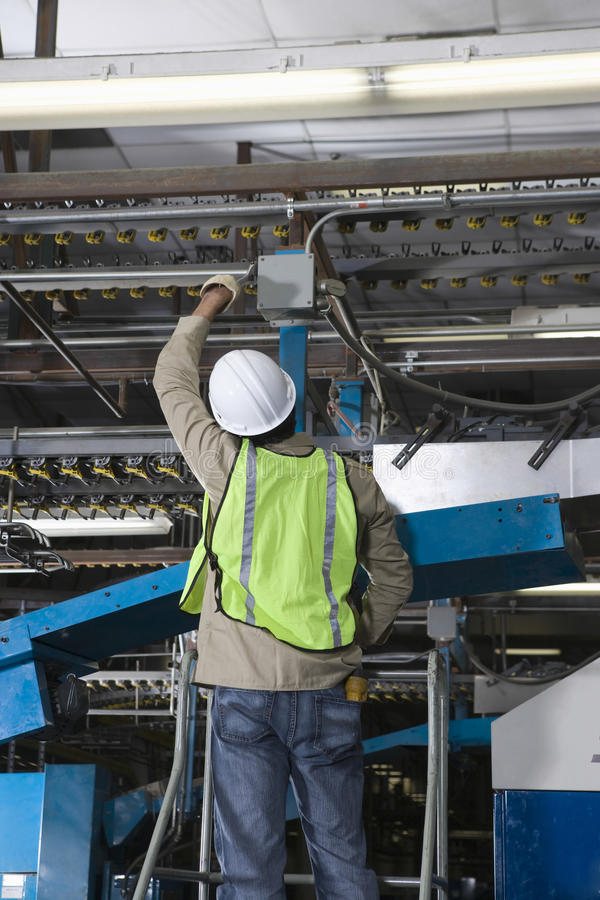 Man som arbetar i tryckpressfabrik arkivbilder