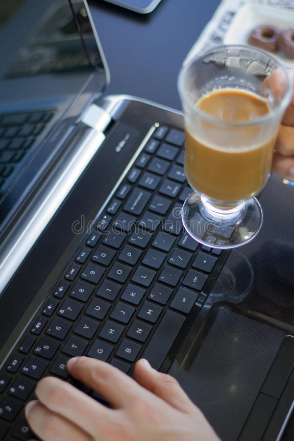 Man som arbetar med en bärbar dator och ett kaffe royaltyfria foton