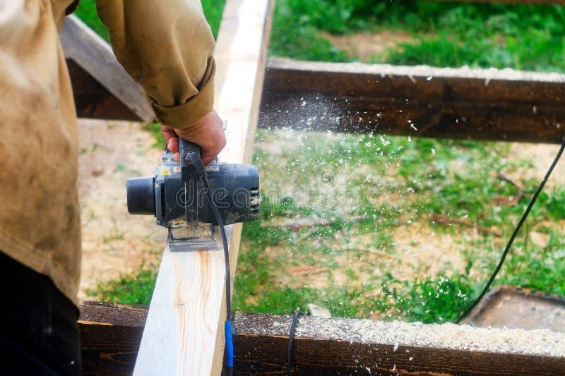 Man som arbetar med en elektrisk hyvlare Att bearbeta av trämaterial, shavings och sågspån sprider i olika riktningar royaltyfria foton
