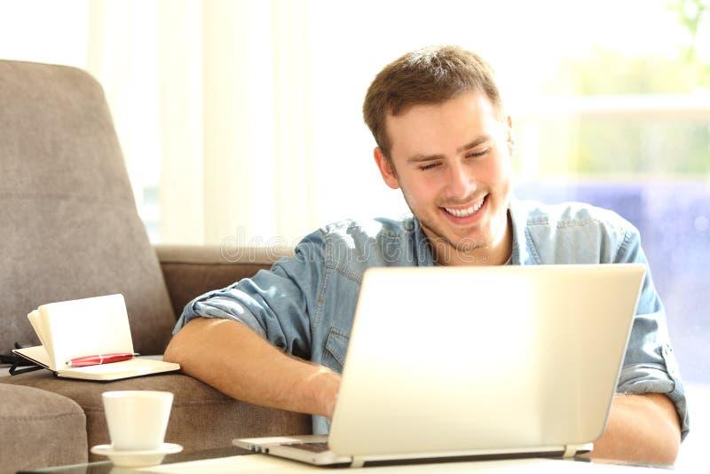 Man som arbetar med en hemmastadd bärbar dator arkivfoton