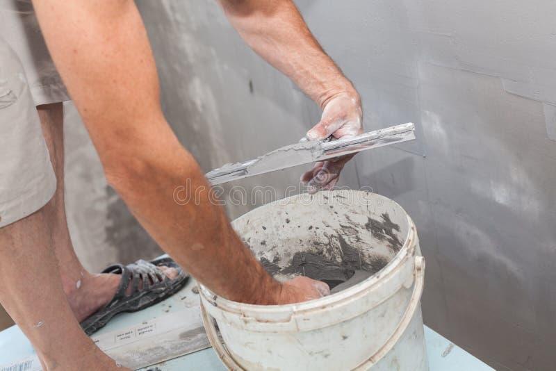 Man som arbetar med en metallspatel och en förberedd grout eller ett bindemedel, när göra murbruk arkivbilder