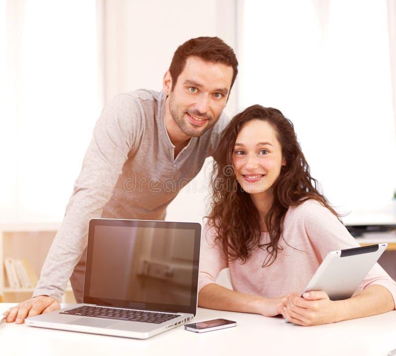 Man som arbetar med hans medarbetare på datoren royaltyfri foto