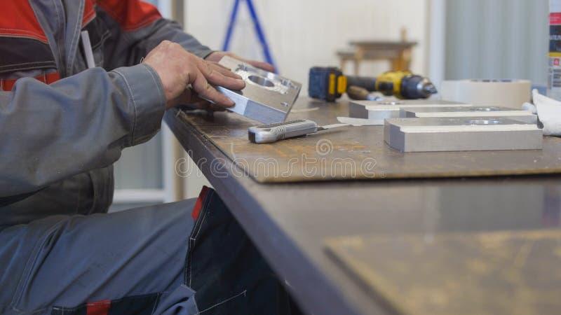Man som arbetar med metallobjekt för tillverkning av industriellt CNC-maskineri royaltyfria foton