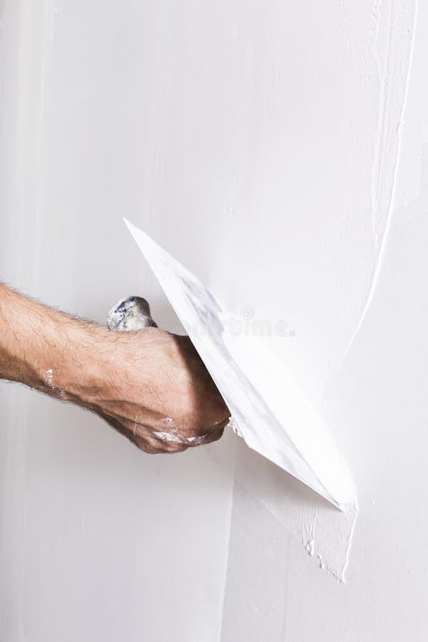 Man som arbetar med mursleven Renovera hemmiljön arkivbild