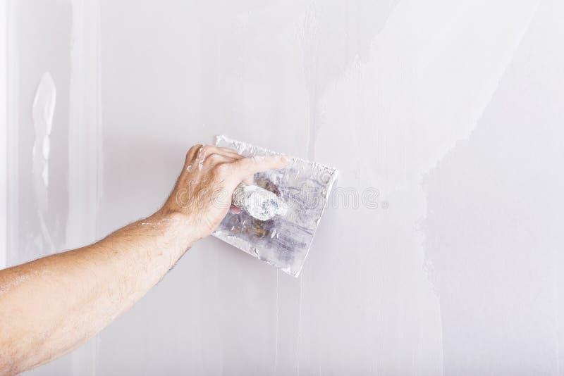 Man som arbetar med mursleven Renovera hemmiljön royaltyfria foton