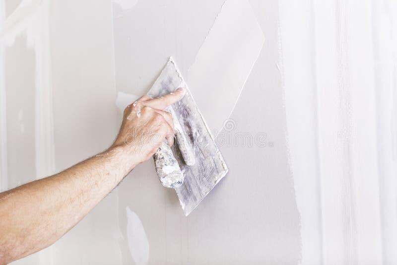 Man som arbetar med mursleven Renovera hemmiljön royaltyfria bilder