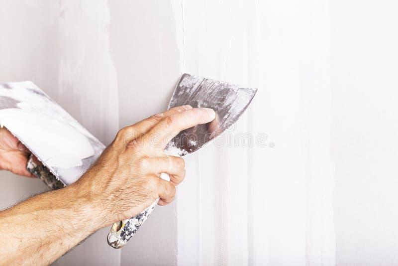 Man som arbetar med spateln Renovera hemmiljön royaltyfri fotografi