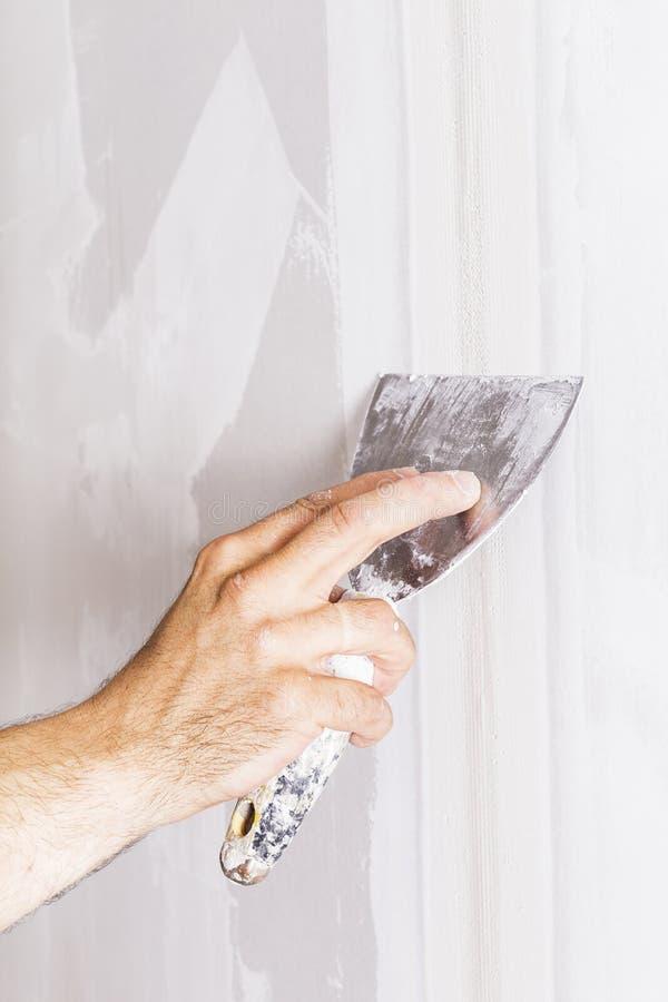 Man som arbetar med spateln Renovera hemmiljön royaltyfria foton